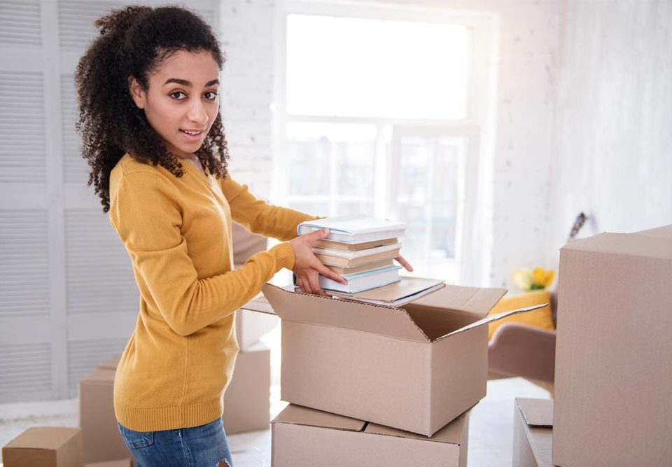 young woman packing to move to college